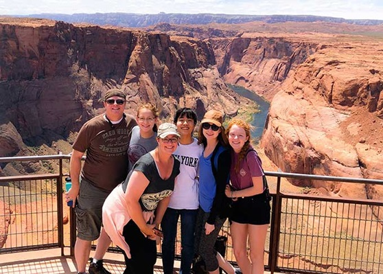 Student and her host family take a picture in front of the Grand Canyon