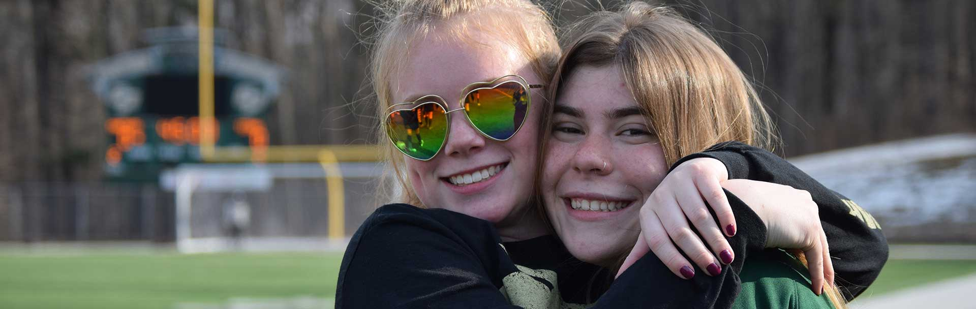 Friends hug after a high school soccer game