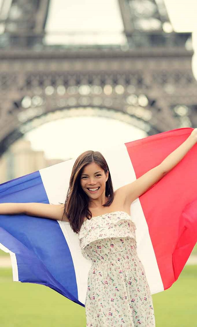 Student with the French flag in front of the Eiffel Tower.