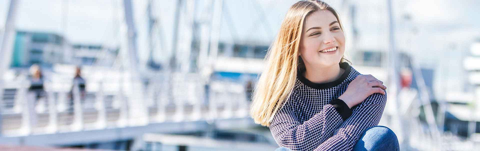 Girl sits by the dock in New Zealand