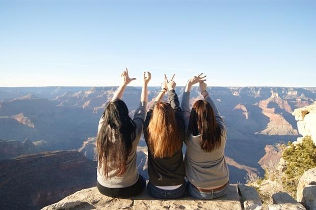 kolme vaihto oppilas grand canyonilla kurkottelee taivaaseen