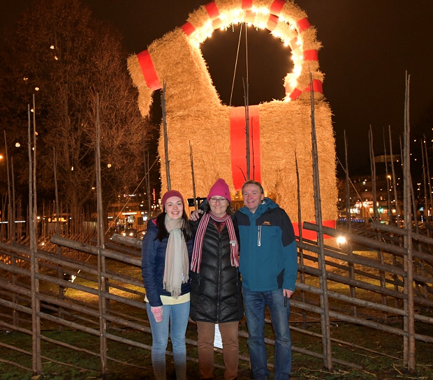 Värdfamilj med utbyteselev framför julbock