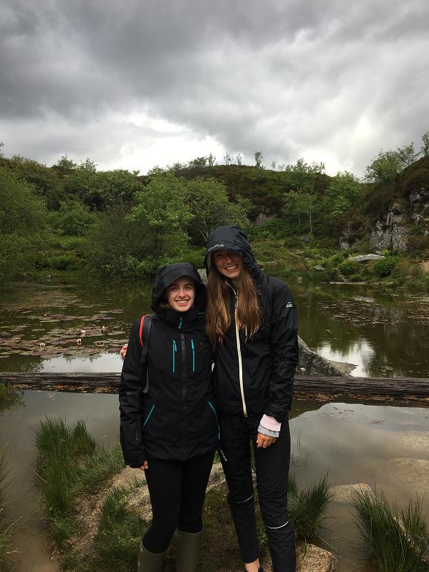 Två utbytesstudent poserar i regnjackor