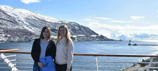 Exchange student and host sister in front of mountain and ocean