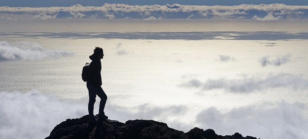 Guy walking on a mountain top surrounded by clouds in Reunion