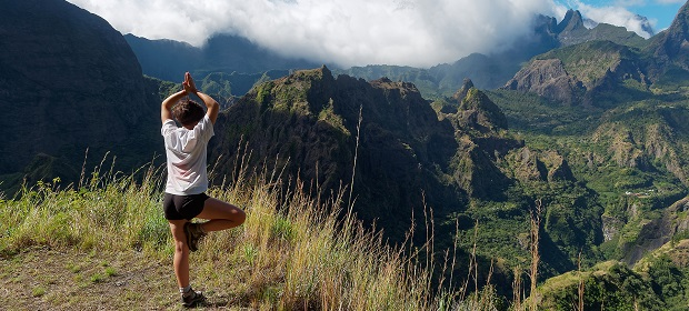 Student doing a yogapose on top of a mountain while looking out at the surrounding mountains
