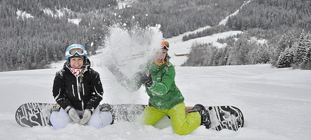 Zwei Mädchen mit Snowboards im Schnee