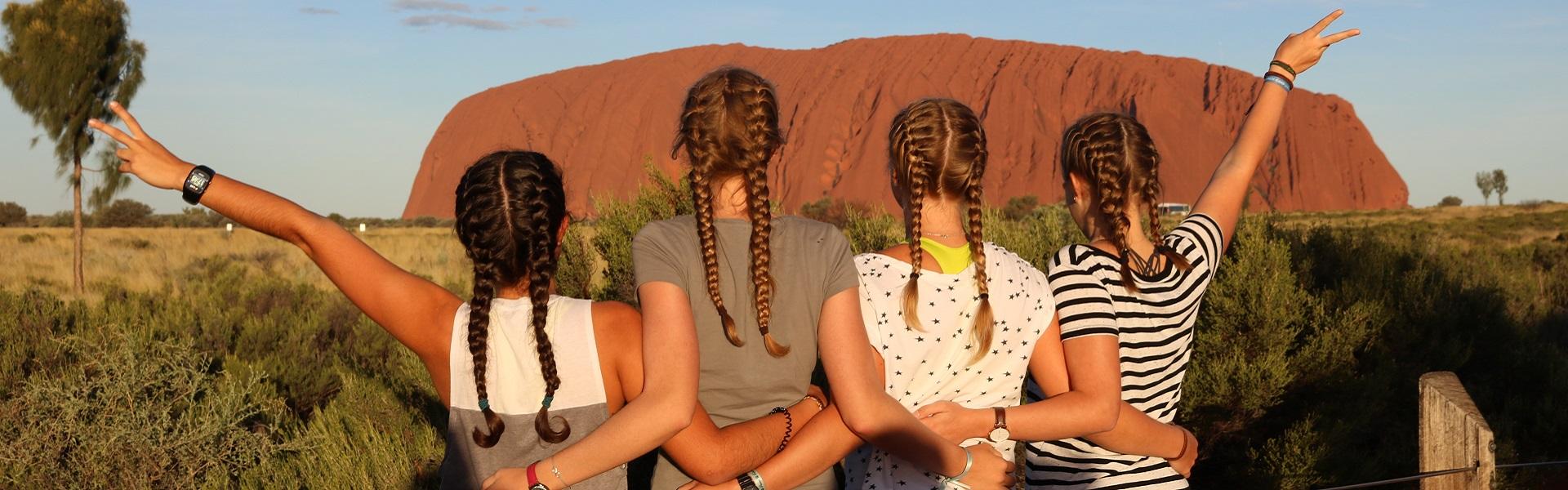 vier Mädchen mit verschränkten Armen vor dem Ayers Rock