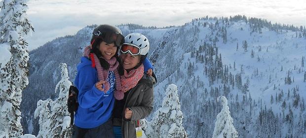 Zwei Mädchen mit Skihelm in verschneiten Bergen