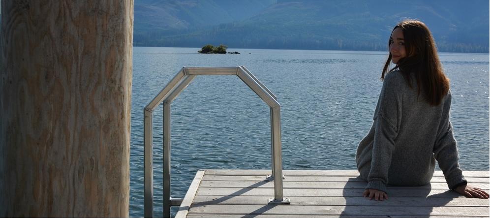 Mädchen sitzt auf einem Steg am See
