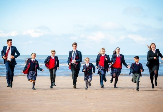 Students running on the beach at Rossall School