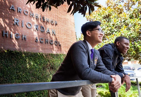 2 boys smiling in front of a sign at Archbishop Riordan High School California