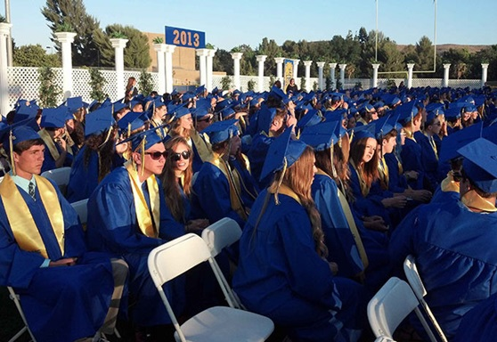 Students in graduation gowns and caps sitting down