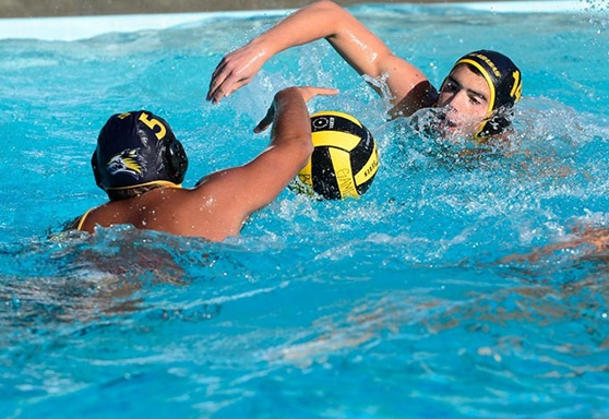 2 high school students playing water polo