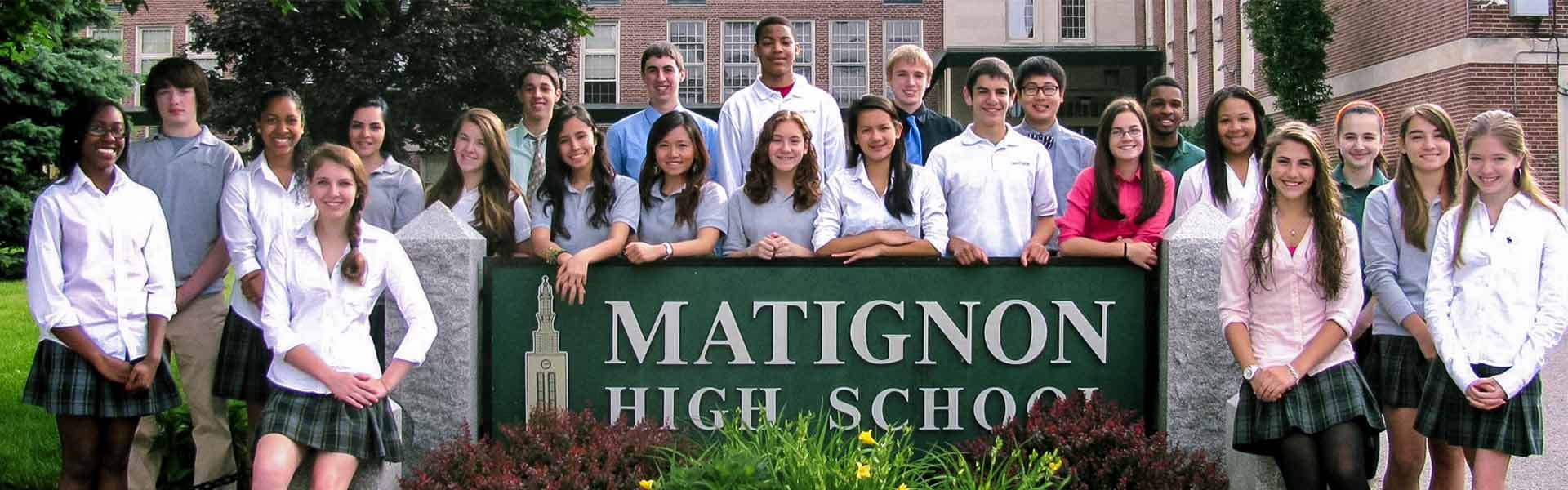 Group of high school students smiling in front of a sign reading The Cambridge Matignon School