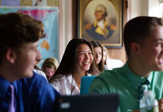 High school students smiling in a classroom