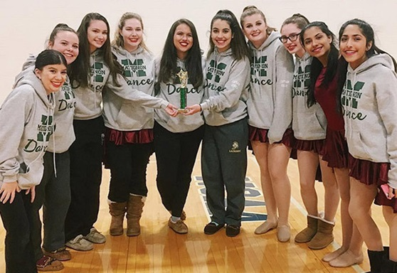 A dance team smiling in a gym hall