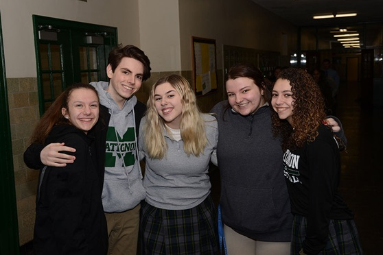 Group of high school students smiling in a school hallway