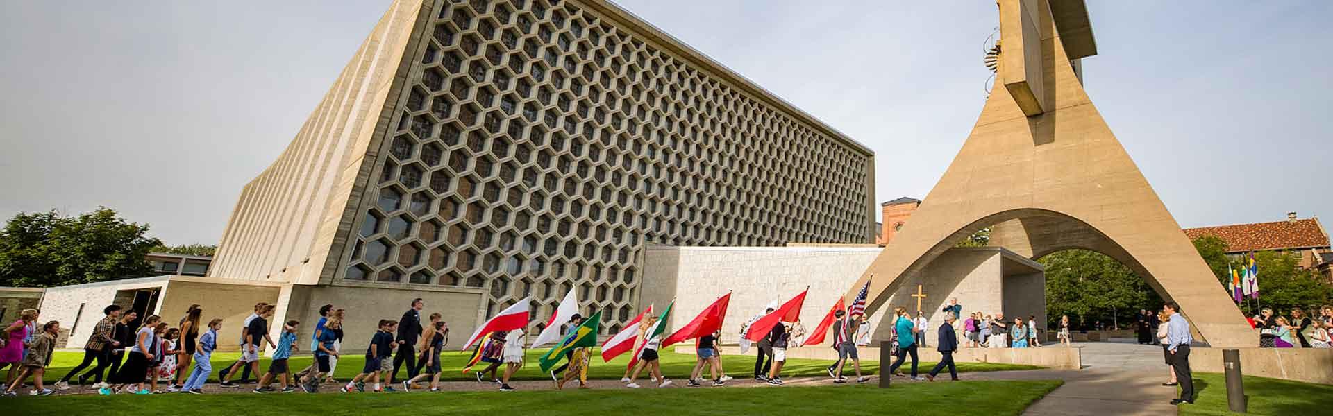 Students holding flags walking across campus at Saint John's Preparatory School