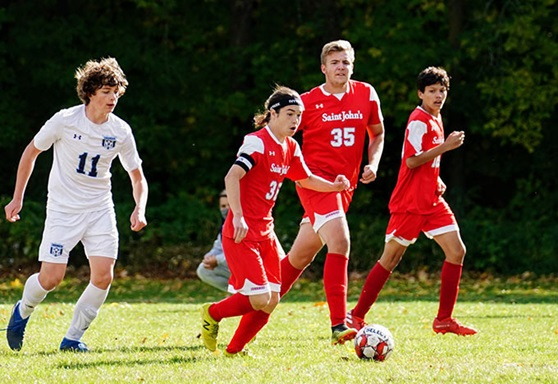 Boys playing football outdoor at St Johns Preparatory High School in Minnesota USA