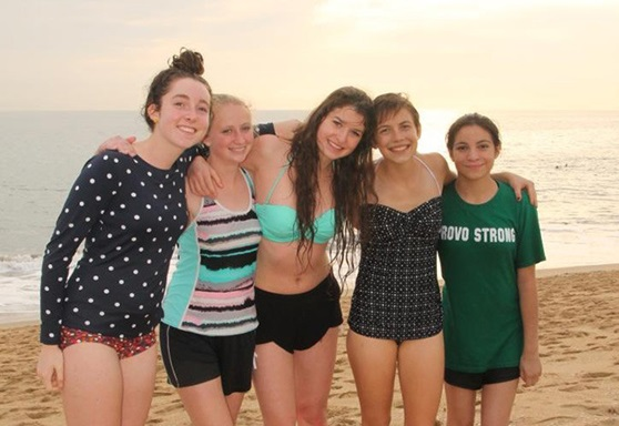 Teenage girls smiling on a beach at sunset