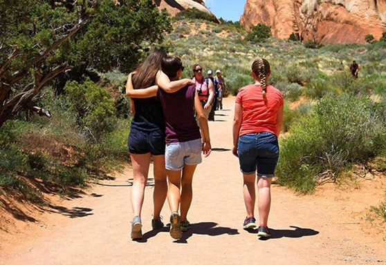 3 people hiking on a trail in the desert
