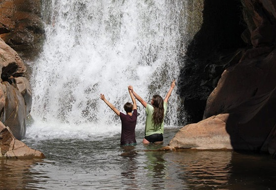 2 people standing under a waterfall