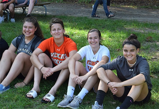4 high school students smiling and sitting on grass Vermont Academy